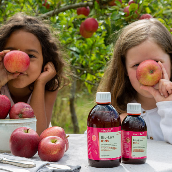 Microbz home: two girls sat outside at a table with Bio-Live Kids and apples and making silly faces