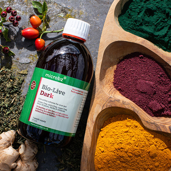 Our unique formula: a bottle of Bio-Live dark led down next to herbs