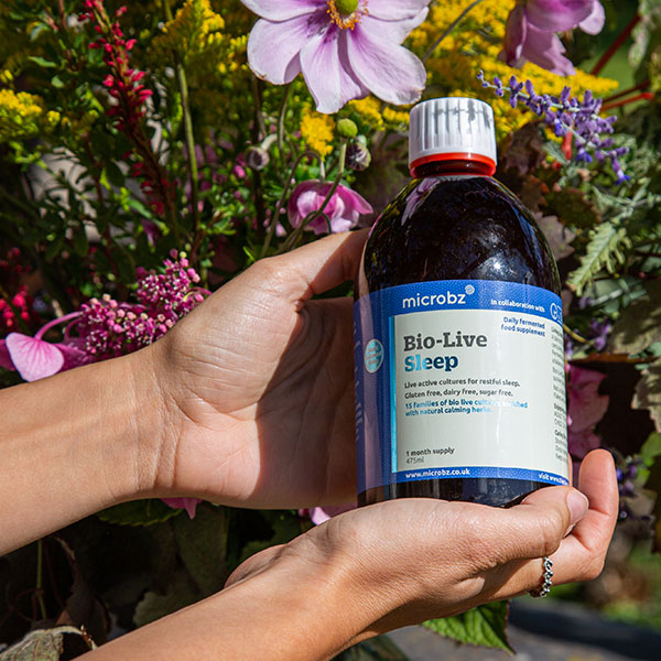 Our unique formula: Someone holding a bottle of Bio-Live Sleep outside in nature close up