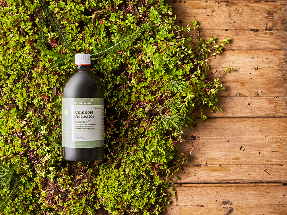 An image of a bottle of liquid compost activator lying on a bed of moss