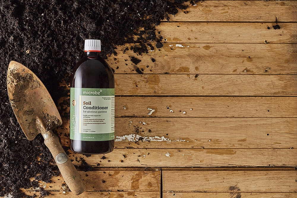 An image of a bottle of soil conditioner with some soil and a trowel